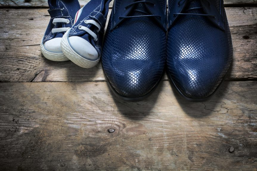 Adult men's shoes positioned next to child's shoes on a wooden floor.