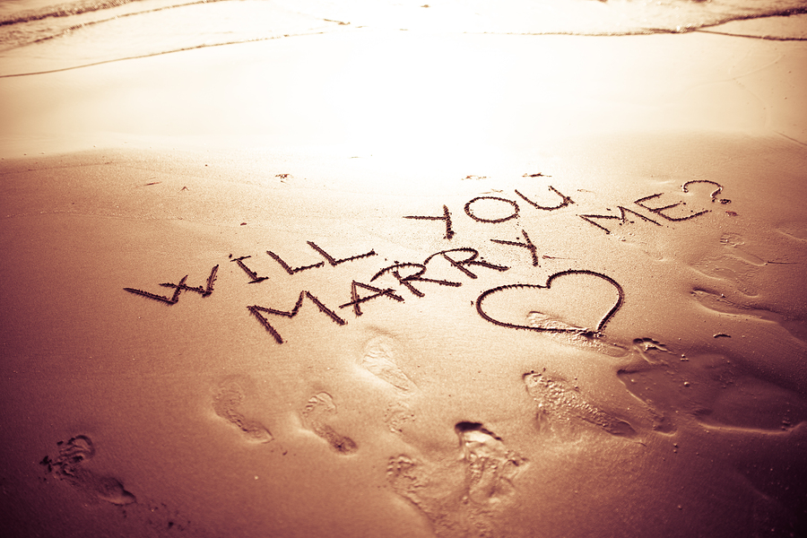 "The message ""Will You Marry Me?"" with a heart below it written in sand."