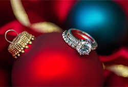 A red holiday ornament with a set of diamond wedding rings resting on top.