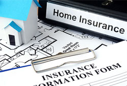 A small paper home, a binder labeled Home Insurance, and an Insurance Information Form on a clipboard sit on top of paper blueprints for a home.