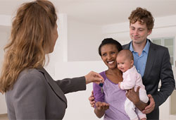 A woman handing a key to a family while standing in an empty white room.