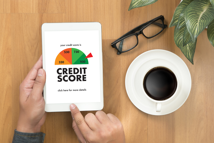 Overhead view of a table, in view is a man's hands holding a tablet with a credit score of 930 on it, also in view are glasses, a cup of coffee, and a houseplant.