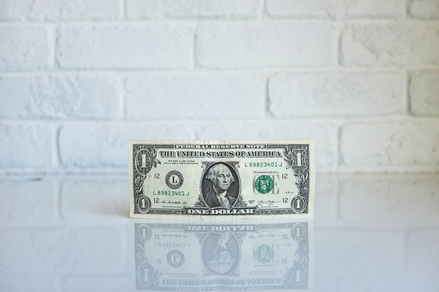 dollar bill on white brick background