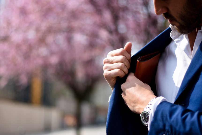 man putting wallet in suit pocket