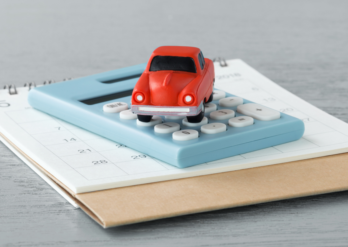 toy car sitting on a calculator and calendar
