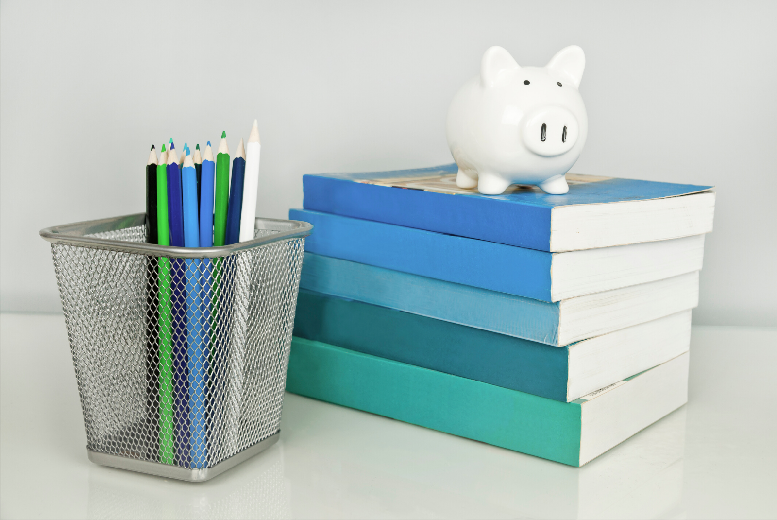 Piggy Bank on Books with pens in a pen holder
