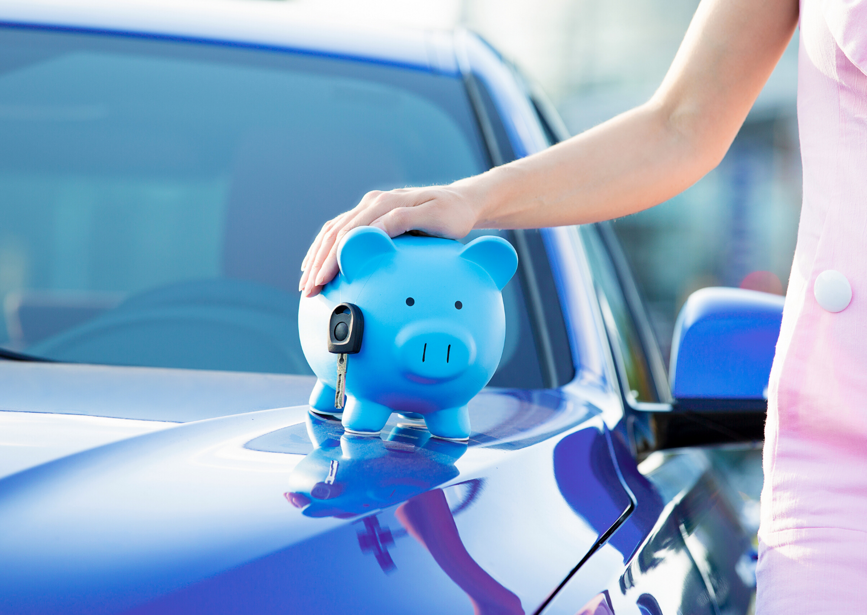 person holding blue piggy bank sitting on car with car keys