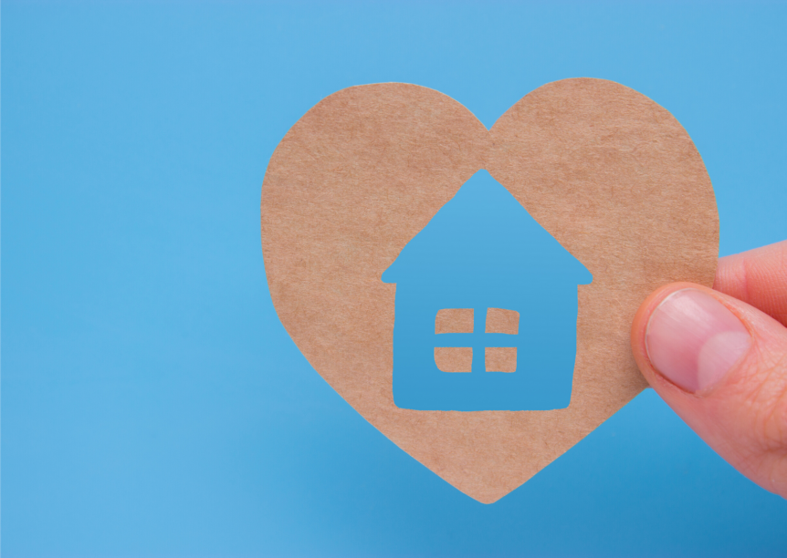 paper heart with house cut out in the middle on blue background