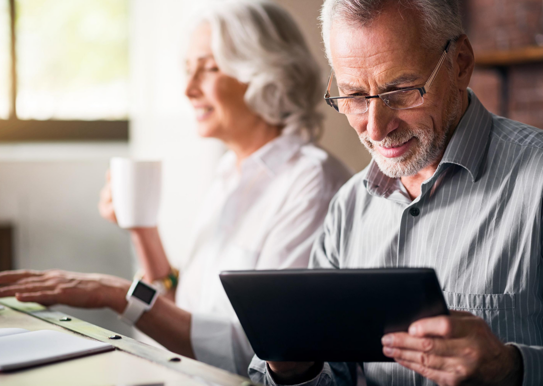 older couple looking at devices, drinking coffee