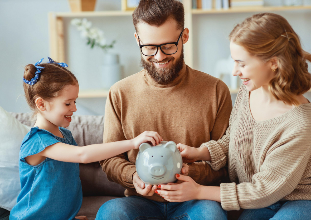 parents holding piggy bank with daughter putting in a coin