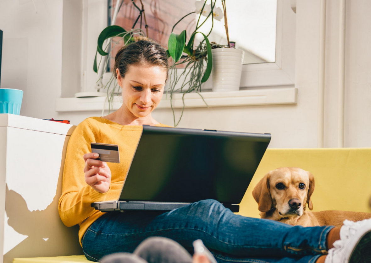 woman holding credit card, sitting on couch looking at her laptop with dog sitting next to her