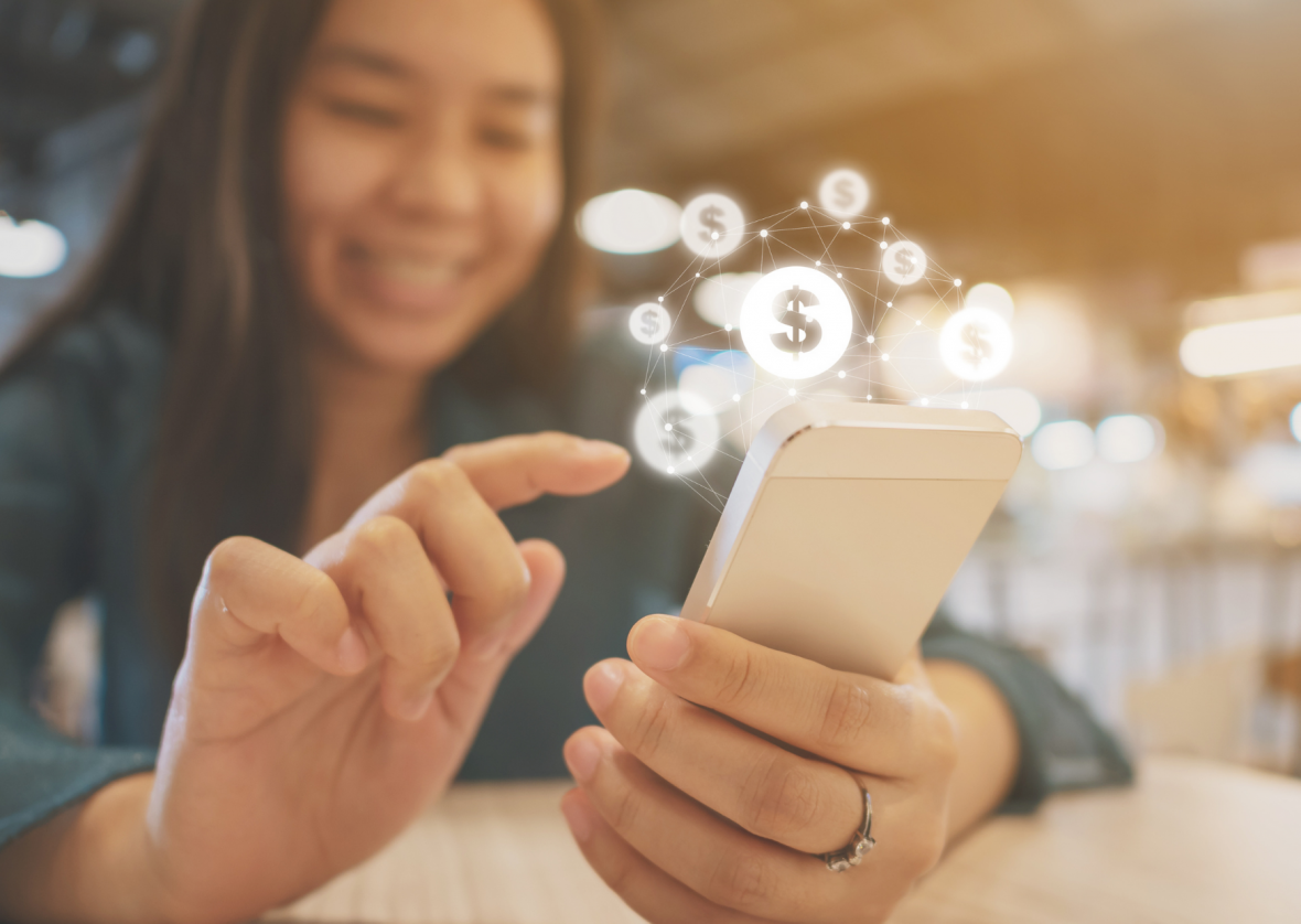 close up of young woman typing on her phone with illustration of dollar sign bubbles radiating from the phone