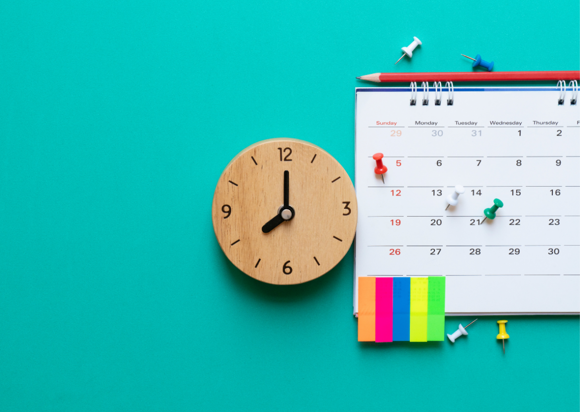 calendar against blue background with a wooden clock, post it notes and pins as reminders