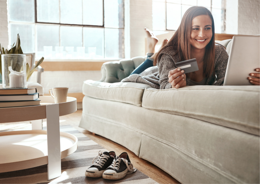 woman using her credit card while on her tablet, laying on her couch