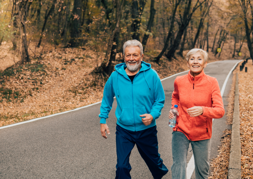 older man and woman running on a road in fall