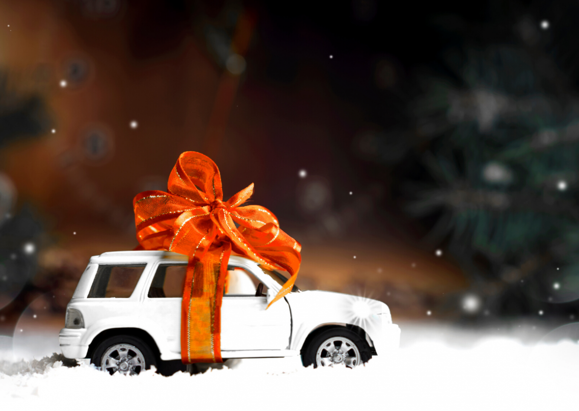 miniature car with big orange bow tied around it. winter woods background