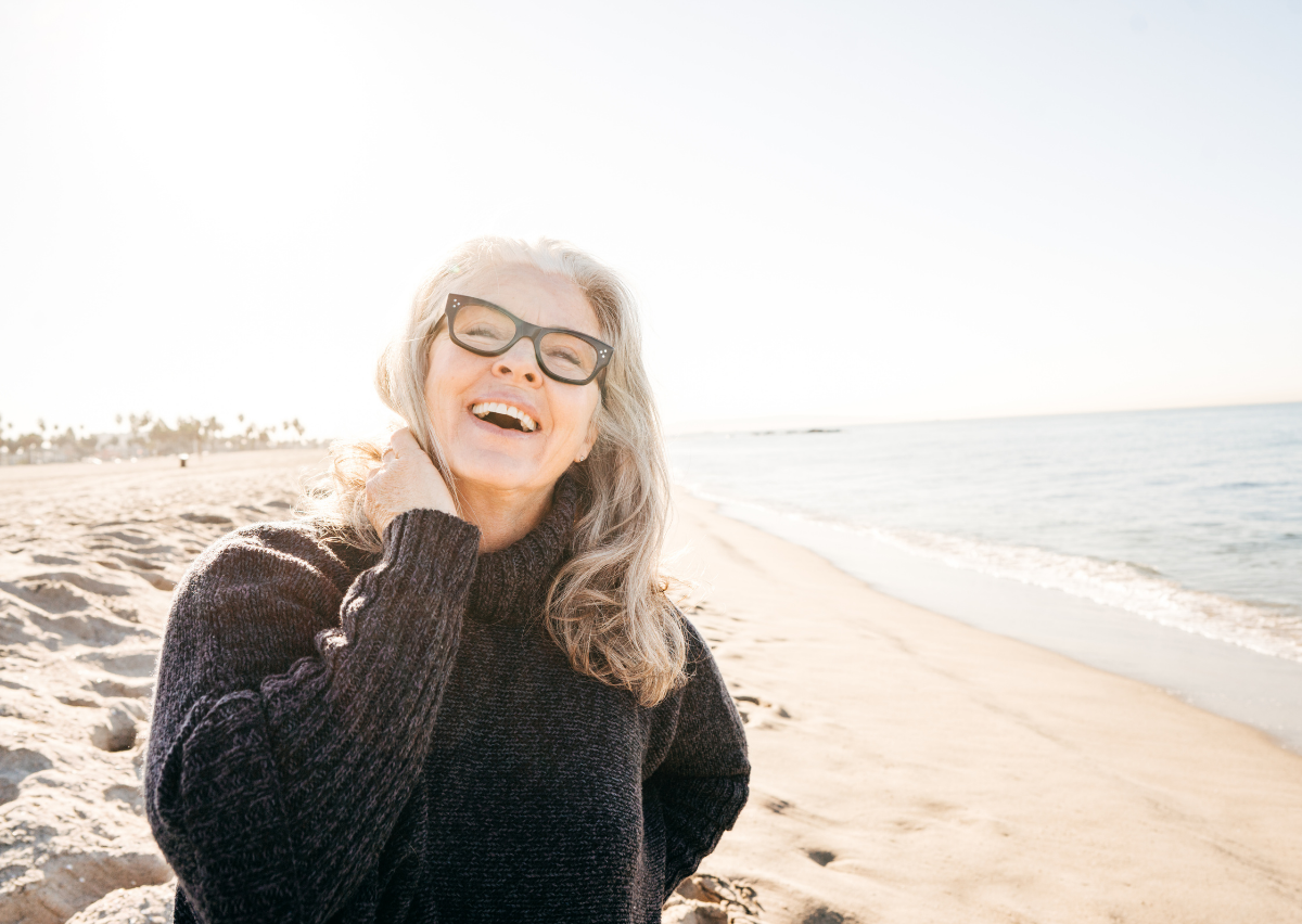 woman with glasses black sweater and grey hair at the beach smiling