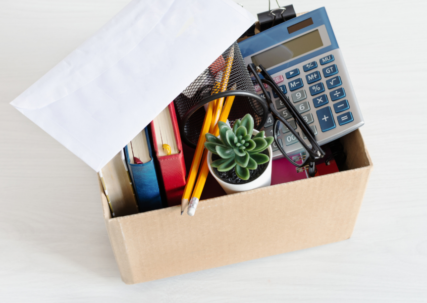 box of office supplies and a pink slip envelope
