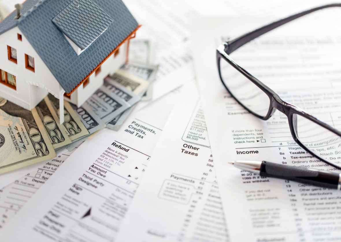 tax forms with model house, several $20 bills, glasses and a pen