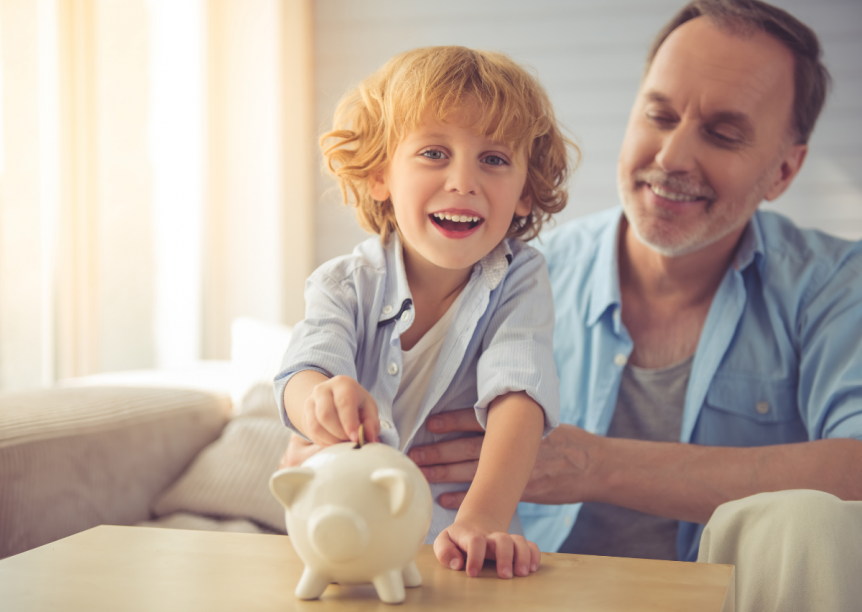 man with young child holding money over a piggybank