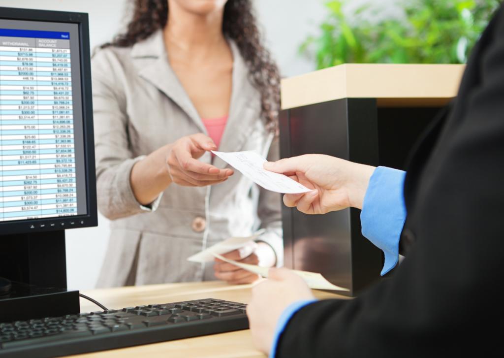 bank teller handing a member a check at the teller desk