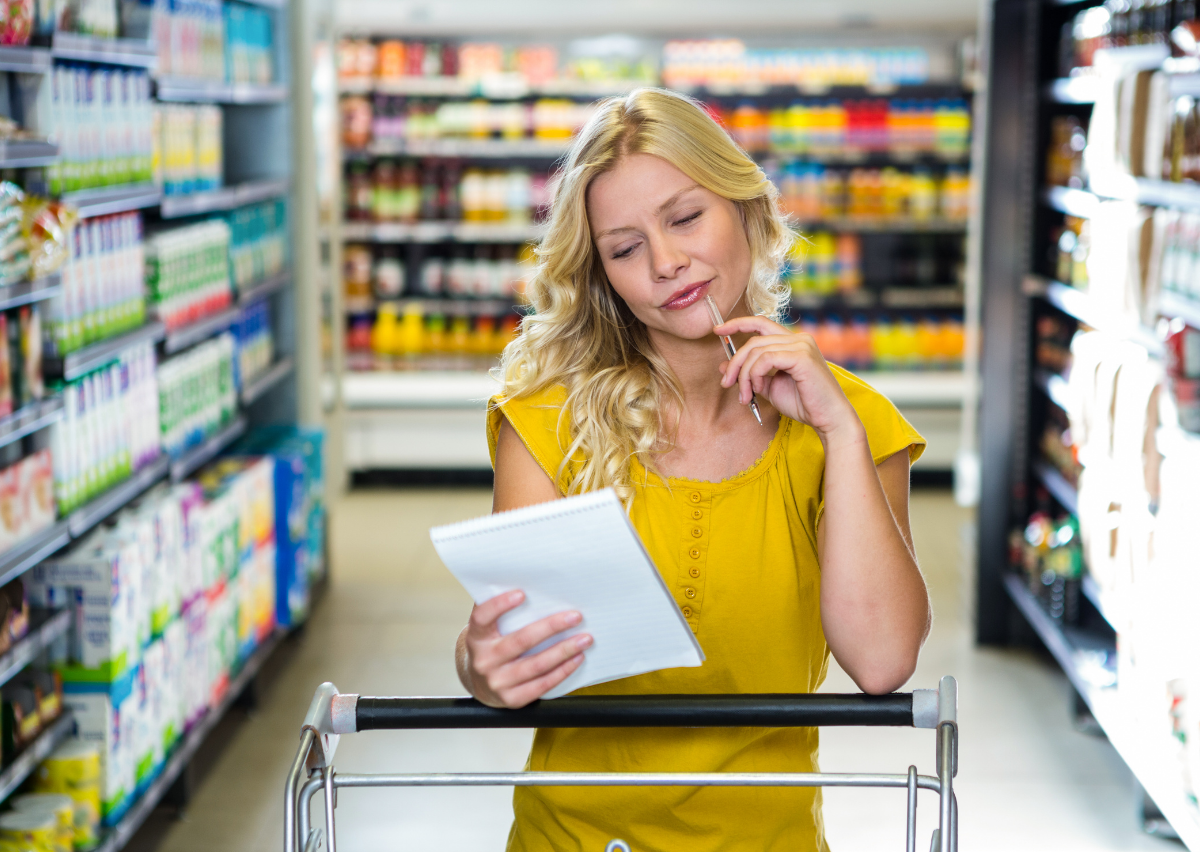 woman with shopping cart considering her grocery list at store