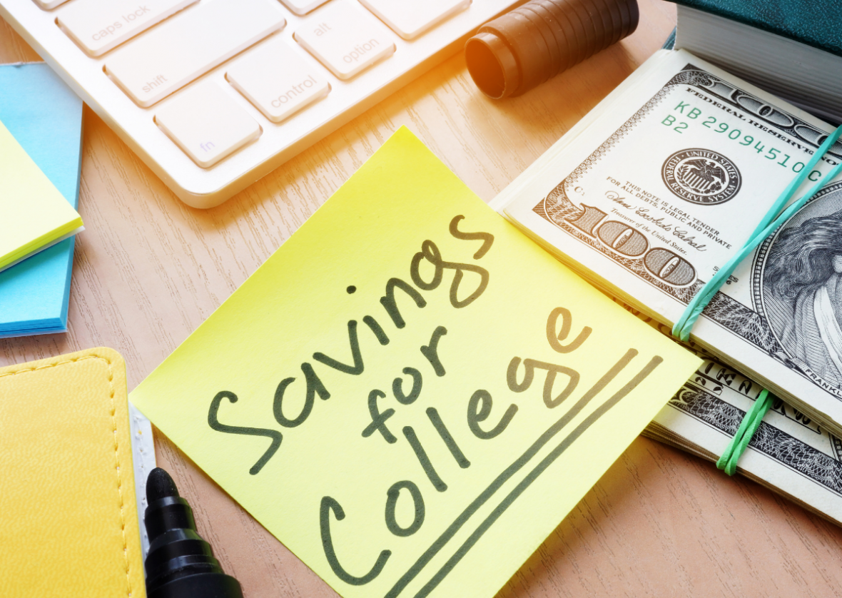 savings for college post-it next to stack of 100 dollar bills on desk with keyboard