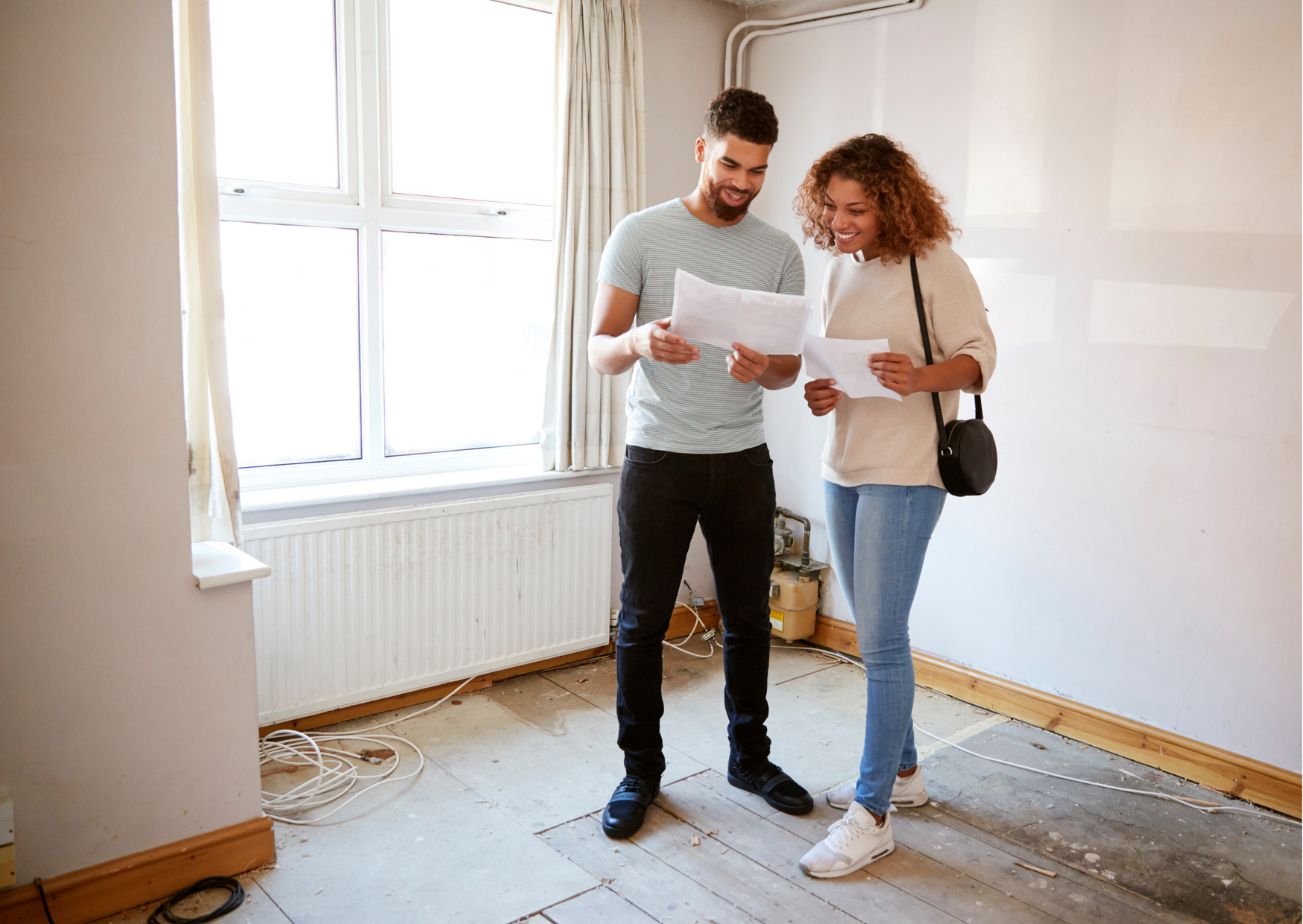couple looking at mortgage application checklist in new house