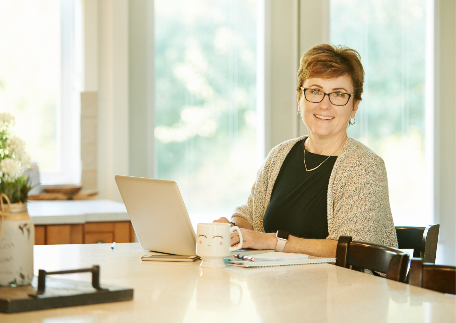 middle-aged woman sitting in front of laptop with cup of coffee, smiling