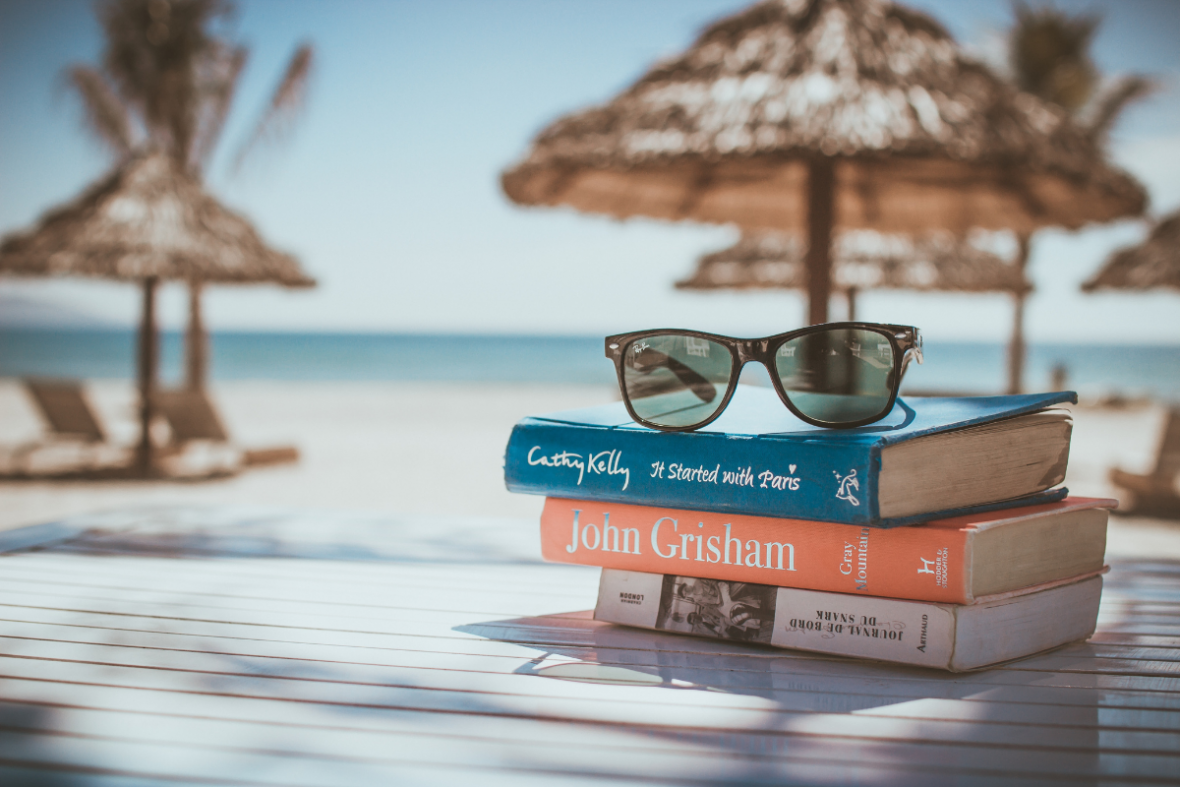 sunglasses on a stack of books at the beach with dried palm umbrellas