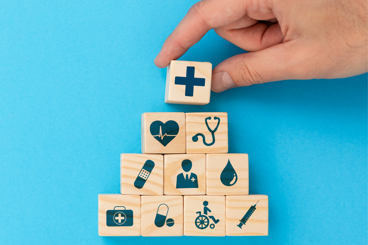 wooden building blocks in a pyramid with health related icons on them