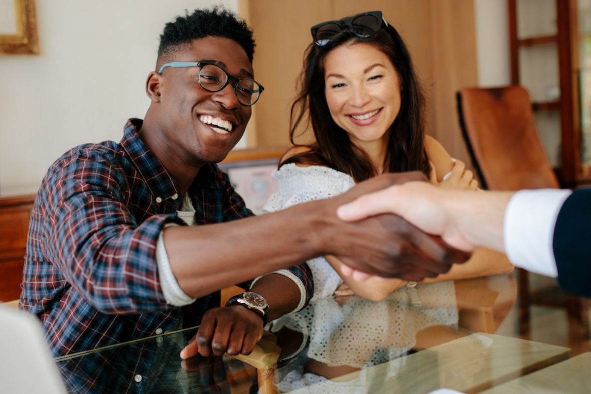 couple shaking hands on purchase in home with a lender