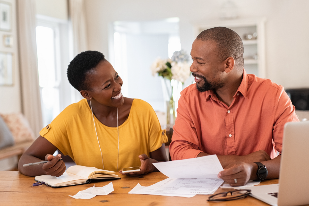 couple discussing finances, looking at papers at home next to computer.