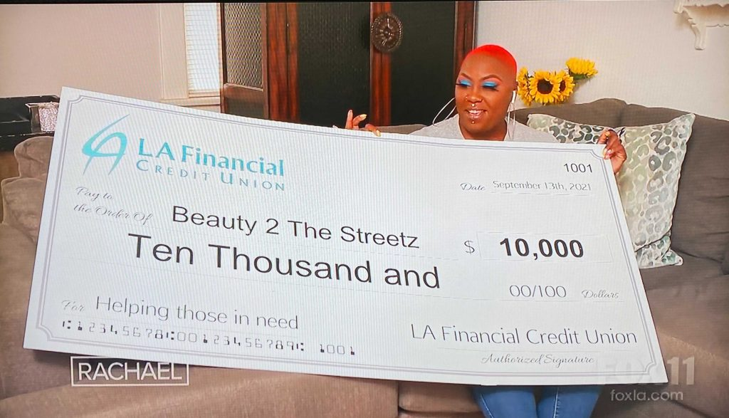 Shirley Raines on The Rachel Ray show, holding a giant check for $10,000 donation to her organization, Beauty 2 The Streets, from LA Financial Credit Union