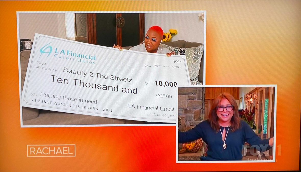 Shirley Raines with Rachel Ray on The Rachel Ray show, holding a giant check for $10,000 donation to her organization, Beauty 2 The Streets, from LA Financial Credit Union