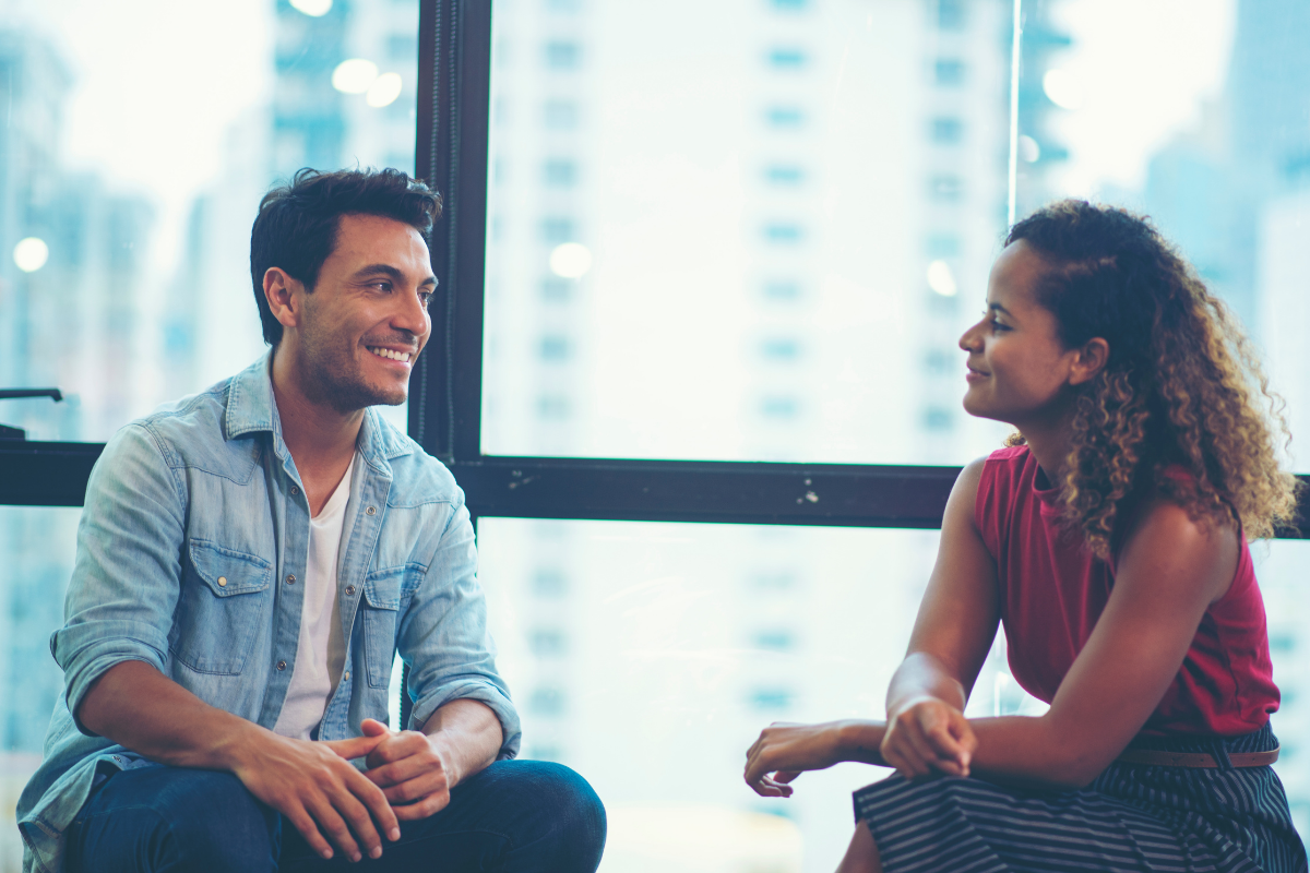 featured image - man and woman talking smiling in front of large city apartment window
